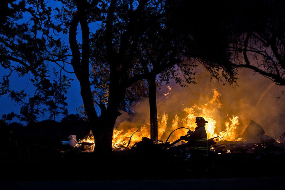 A firefighter drags a water hose closer to a fire in the 300 block of U.S. Business 77 toward Refugio on Dec. 28, 2017. The abandoned home was set on fire by the property owner after he ran into complications with trying to have the home demolished.
