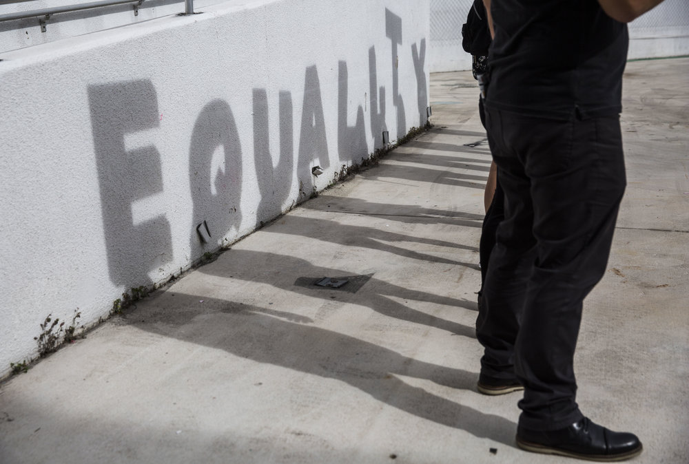 """A shadow spelling out """"equality"""" is cast against a wall as a part of an art piece set up at the Women's March Florida at Mana Wynwood in Miami on Jan. 21, 2018."""
