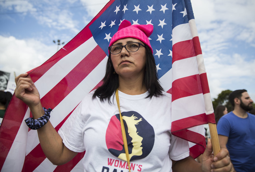 """Vivian Ivalo, 50, who is originally from Argentina but now lives in Miami stands with an American flag during the Women's March Florida at Mana Wynwood in Miami on Jan. 21, 2018. """"I attended this because I feel empowered by the people around me,"""" said Ivalo.""""This is my second march."""""""