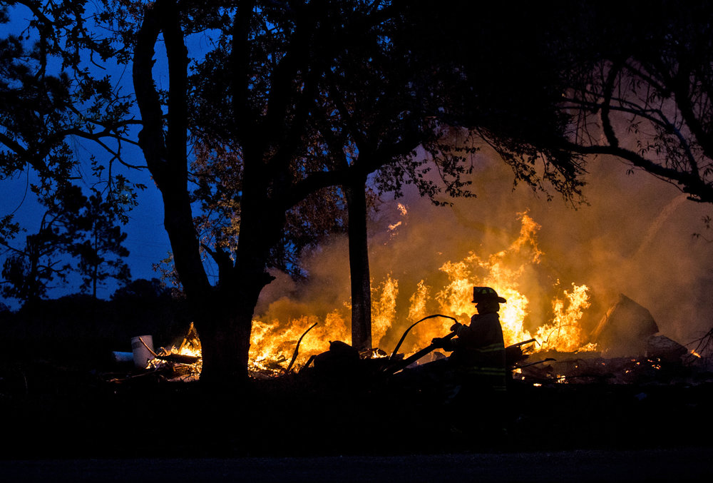 A firefighter drags a water hose closer to a house fire in the 300 block of U.S. Business 77 toward Refugio, Texas on Dec. 28, 2017. The abandoned home was set on fire by the property owner after he ran into complications with trying to have the home demolished.