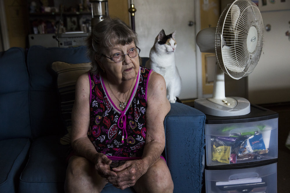 Nadine Butler, 81, sits on her sofa next to her cat Mama Rufus in her home in Victoria, Texas where she is on her eighth day without power or running water since Hurricane Harvey on Sept. 3, 2017.