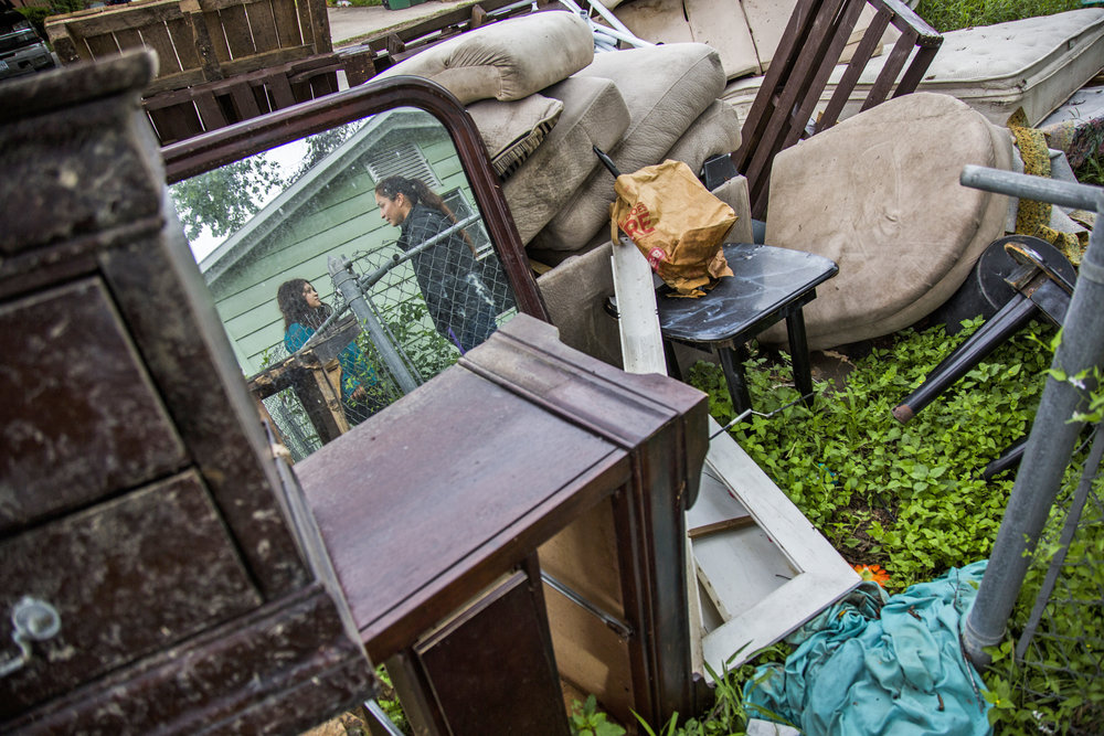 Samantha Torres, 23, left, and Jasmine Monroe, 24, right, stand outside of their home next to a pile of items they were forced to throw out after Hurricane Harvey caused widespread flooding, filling their home with water and damaging most of their belongings.