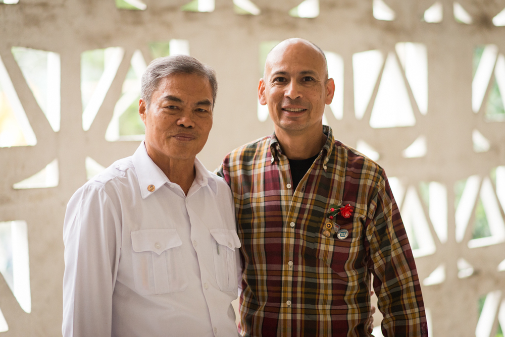 Mr. Xiem with Ron Reyes after the meeting. Mr. Xiem wears the 2 Sides Project lapel pin, as does Ron Reyes, along with his Gold Star pin. Ron also wears a red flower pin. It was made by victims of Agent Orange. Mr Xiem gave each of us a flower pin. Photo courtesy Istrico Productions.
