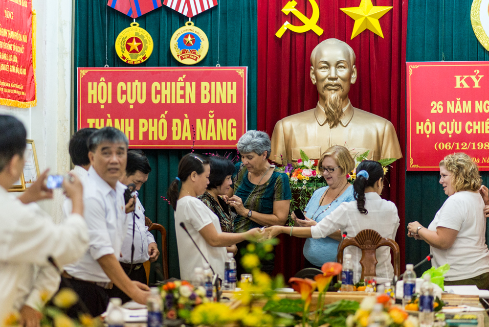 After the meeting, the daughters exchanged pins in front of a bust of Ho Chi Minh in the Da Nang Veterans Hall. Photo courtesy Istrico Productions.