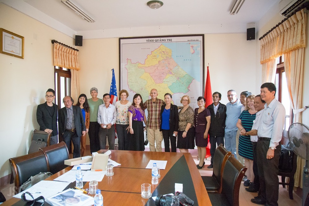 Ms. Thuy, standing on the right in front of the red flag, was one of nine Vietnamese sons and daughters who met with the 2 Sides Project group in Quang Tri. Photo courtesy Jared Groneman.