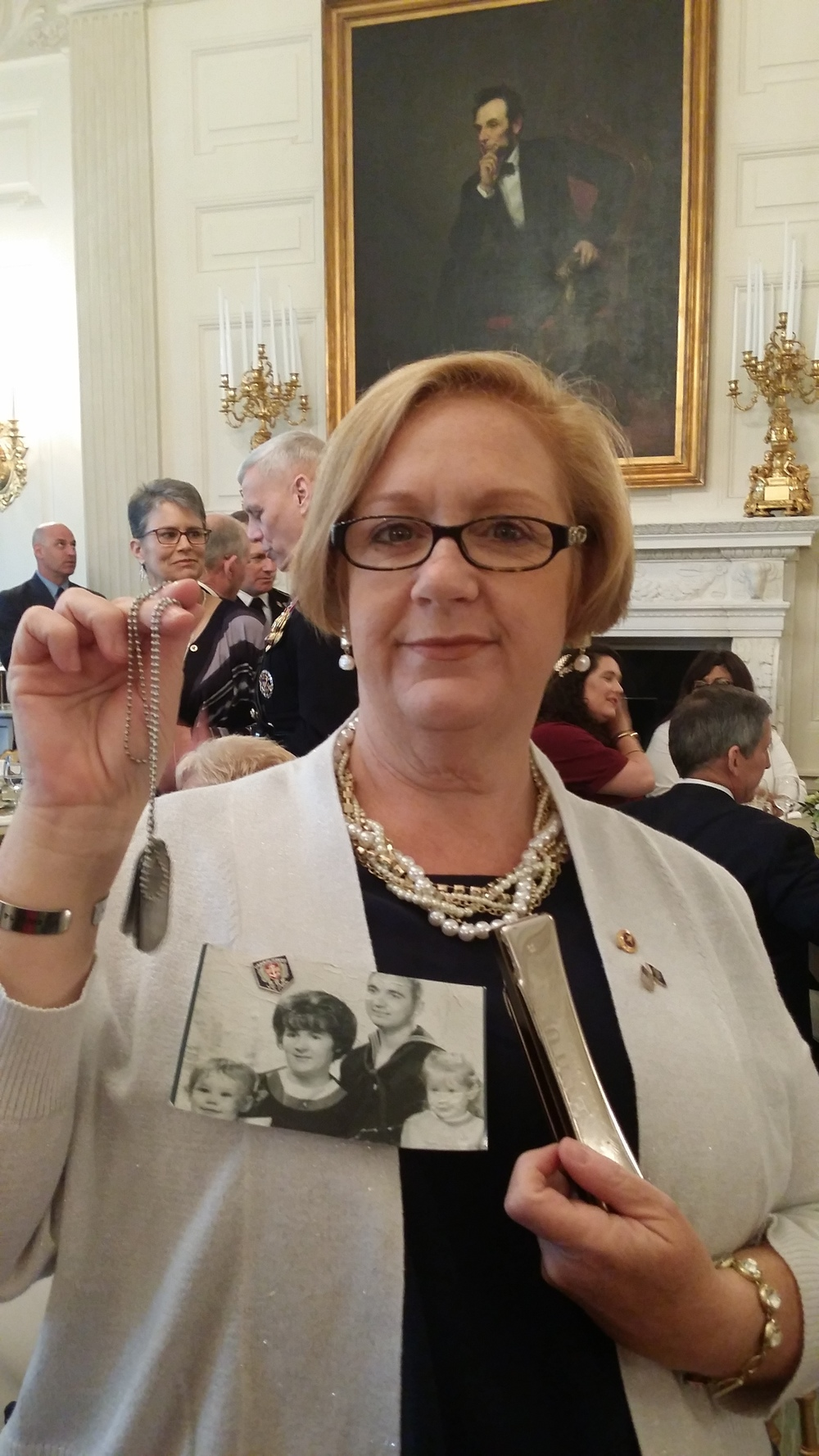 Susan in the Lincoln Room of The White House, where breakfast was held. Her father's harmonica, which was returned from Vietnam, is in her left hand. The dog tags she holds in her right hand, a gift from Jeanette Chervony, bear the names of the fathers of the first six who went on the 2 Sides Project trip to Vietnam.  Photo courtesy Susan Mitchell-Mattera.