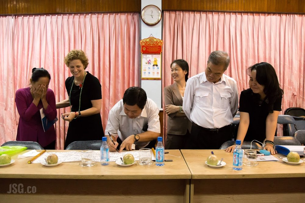 Ms. Diem, far right, shares a laugh as Vietnamese sons and daughters write their thoughts on a keepsake scroll. Photo courtesy Jared Groneman.