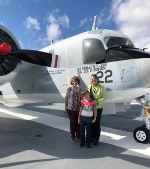 Jill, right, on the USS Yorktown next to a plane named in her father's honor.