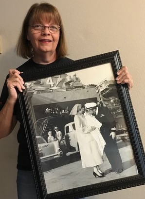 Jill with a favorite family picture of her father saying goodbye before leaving on a deployment on the USS Philippine Sea, 1957