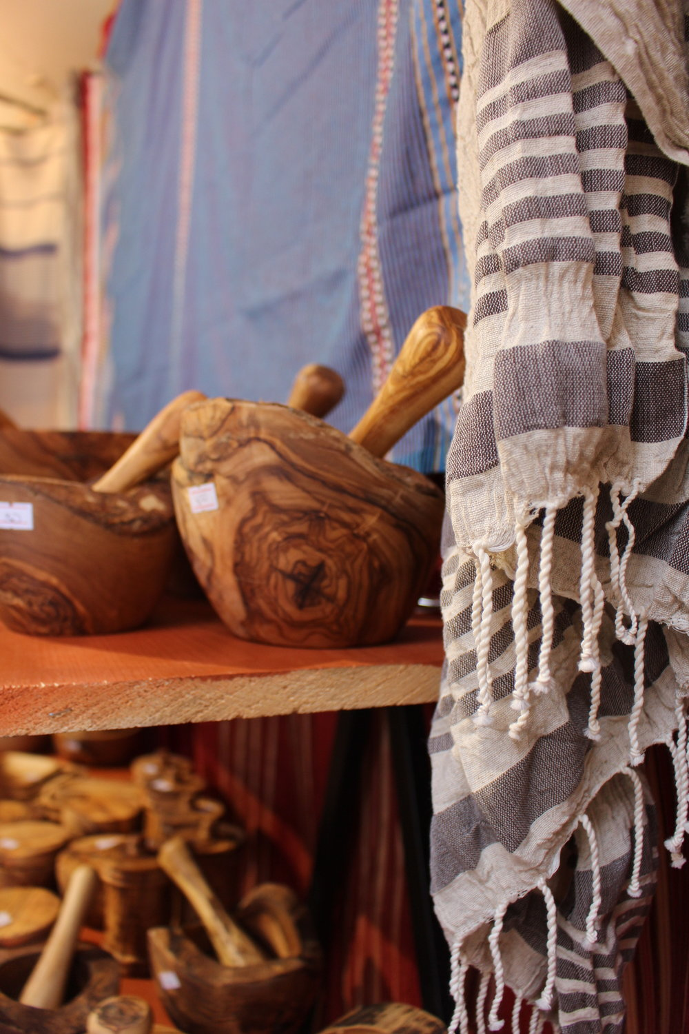 A Tunisian scarf hangs alongside hand made mashing bowl at Naj Alroud's booth at the Downtown Holiday Market in Washington, DC. Photo By Natalie Hutchison