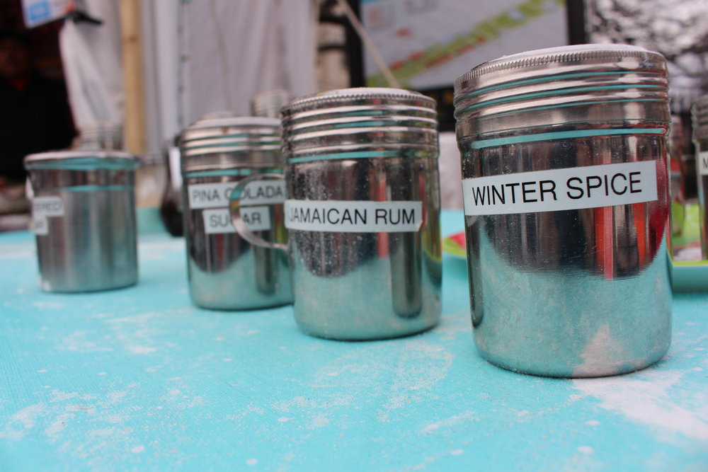 Three of the many powdered sugar flavors at Mgue's Mini's donut booth at the Downtown Holiday Market. Photo by Natalie Hutchison
