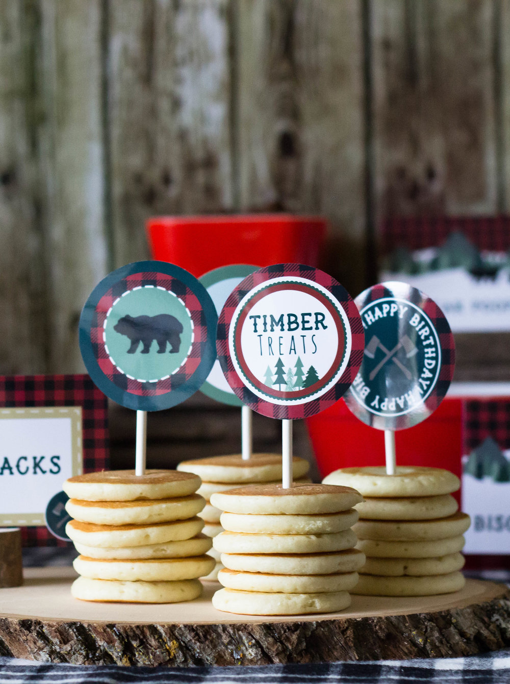 Lumberjack party decor at a rustic first birthday party. Use cupcake toppers on your pancakes to add a fun custom touch. // designs from shopmkkm.com
