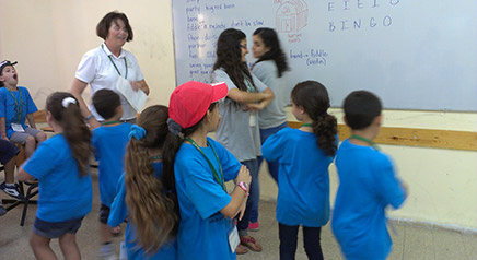 Campers and JCs (Rawan Nseir and Rawan Dahamshy) do-ci-do in Mary Marsh's music class.