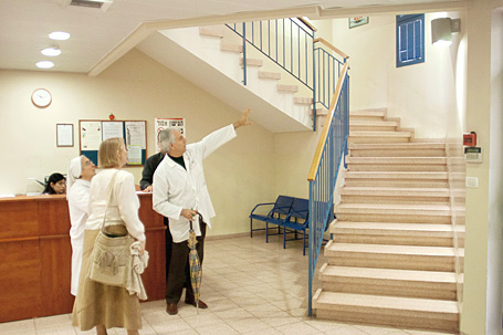Dr. Nakhleh showing the selected 3-wall stairwell for the mural in the Irwin Green Child Development Center