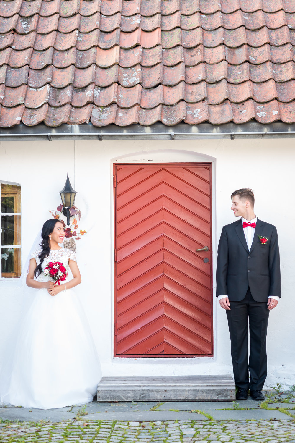 Bride and groom with a red door Stavanger wedding Guillem Cheung Bryllup