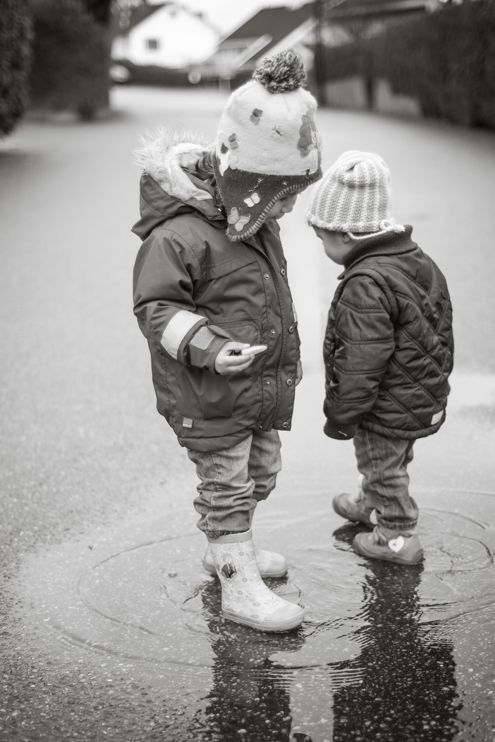 Sisters playing in a puddle BW family photography outdoor Stavanger Familie fotografering