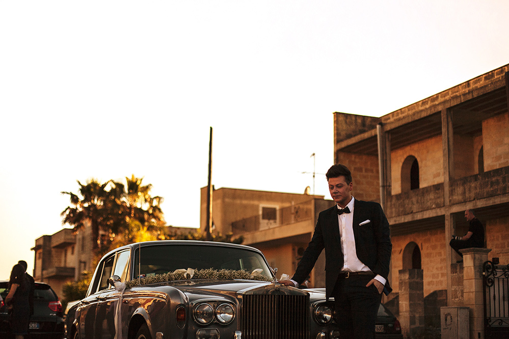 Groom in front of Rolls Royce in Mexico wedding