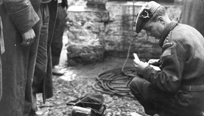 Seaforth Officer, Capt. Keith Murdoch doing an inventory of the effects of German POWs. Possibly in Italy.