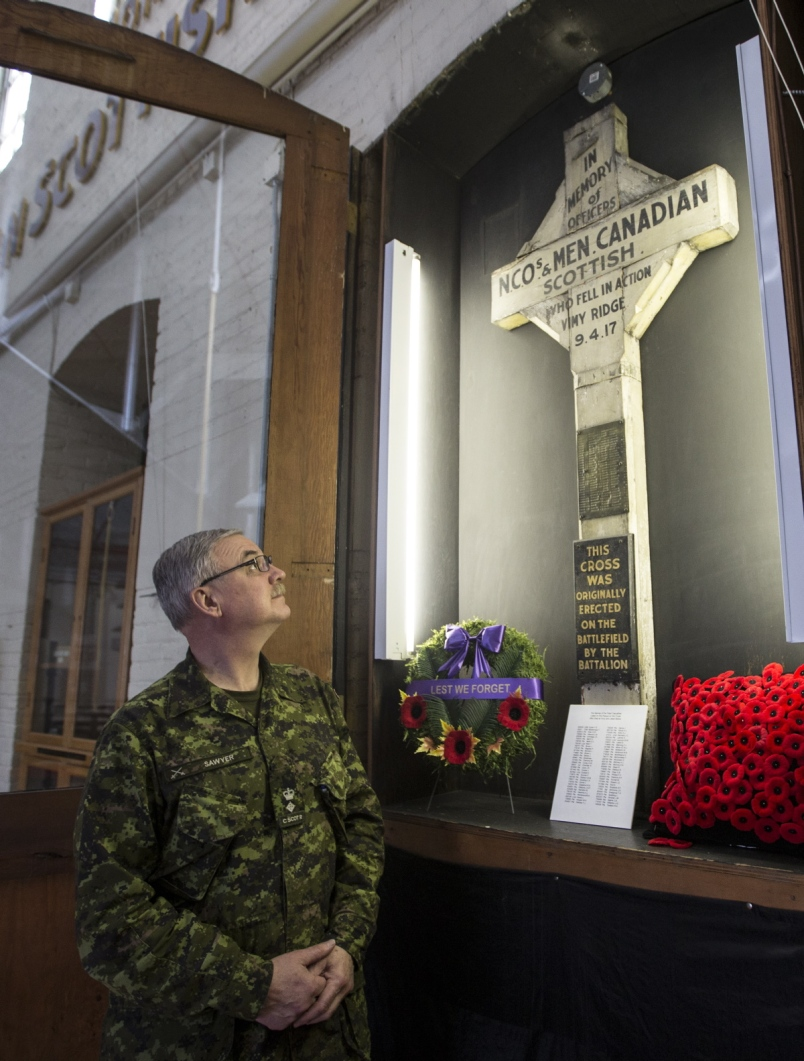 Lt. Col. Stephen Sawyer with the wooden cross at the Bay Street Armoury that was erected by soldiers after Vimy Ridge   Photograph By DARREN STONE, Times Colonist