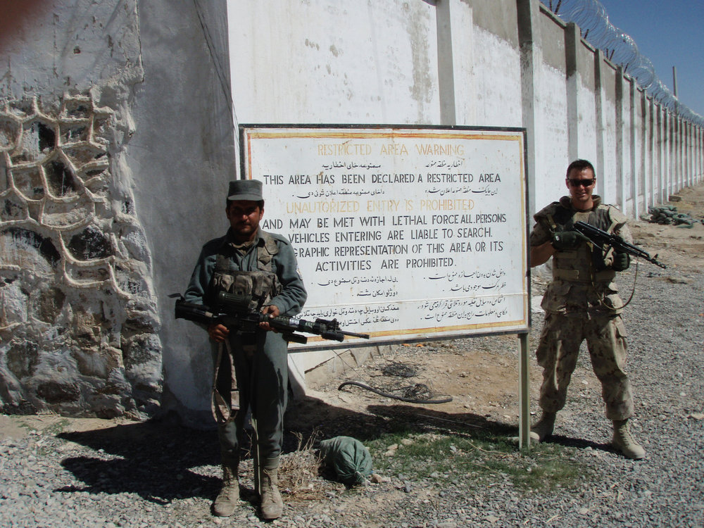 A Seaforth and a member of the Afghan National Police exchange weapons at the front gate of Camp Nathan Smith, Kandahar Provincial Reconstruction Team, Kandahar city. Note the unambiguous warning on the sign.