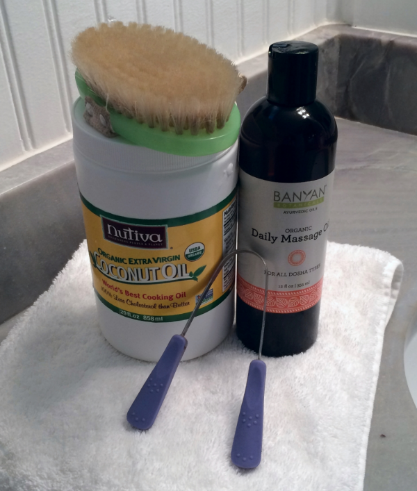 Some of my morning routine supplies: dry skin brush, coconut oil for oil pulling, massage oil, and tongue scraper.