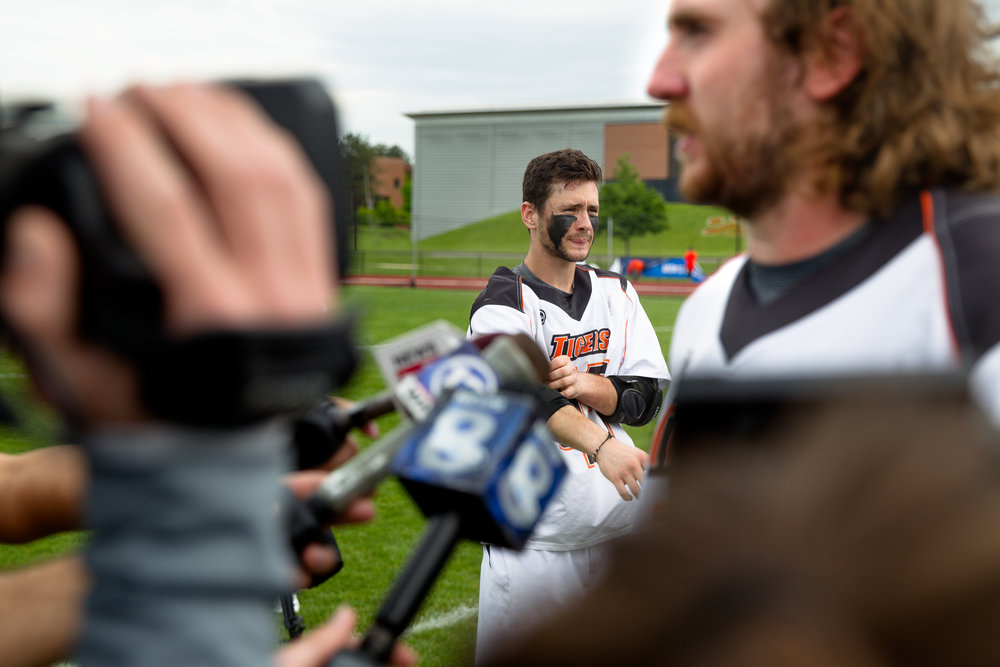 Ryan Lee (left) waits to interview as Chad Levick responds to the media after a NCAA semifinal game.