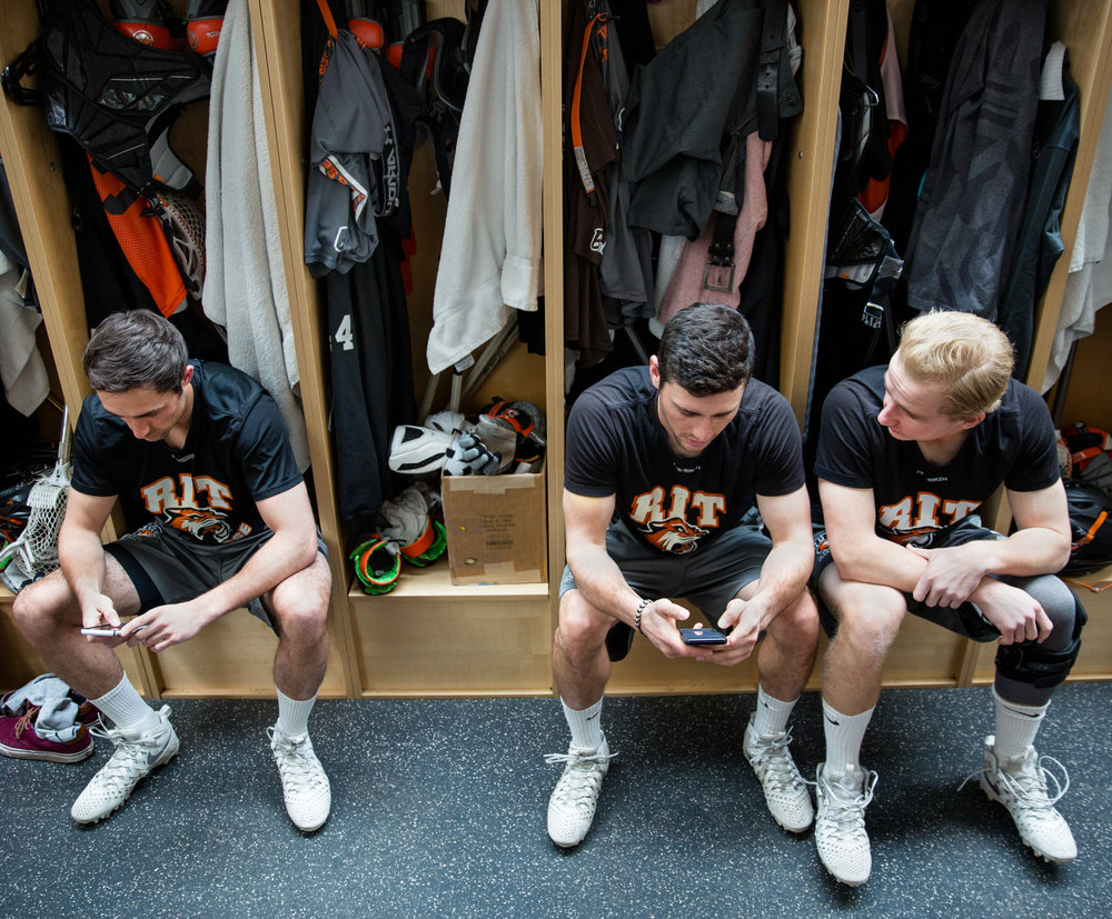 Lee (middle) sits next to Levick's vacant stall in the RIT locker-room before practice. Levick shows up late to practice on Tuesdays due to a conflict with class schedule.