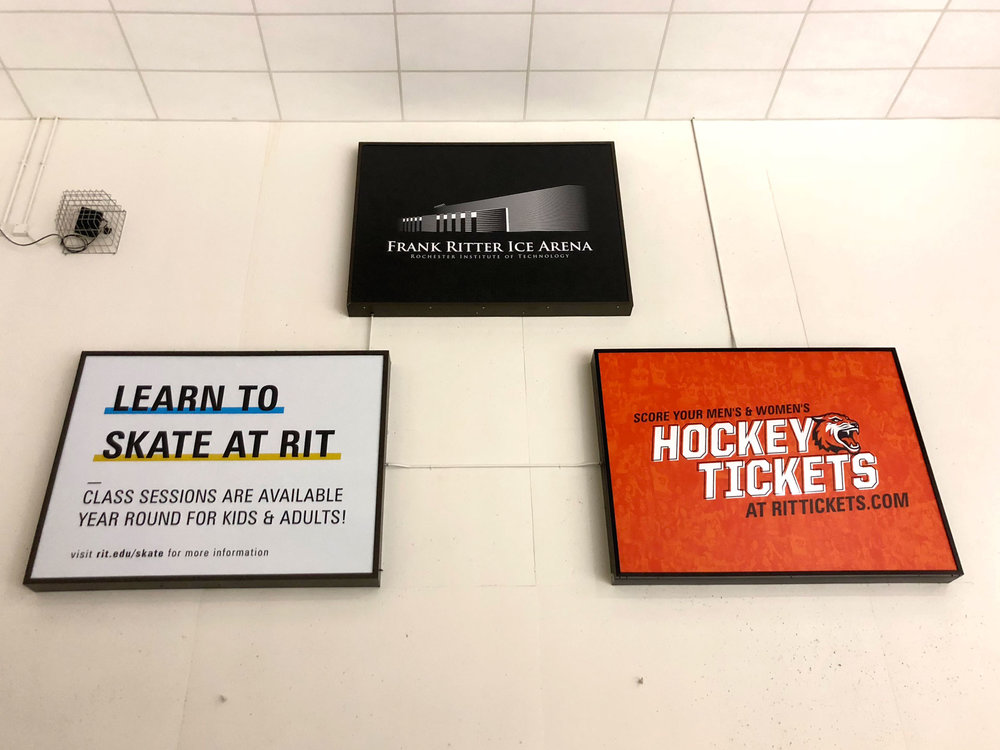 wide view of backlit advertisement signs on back wall of rink