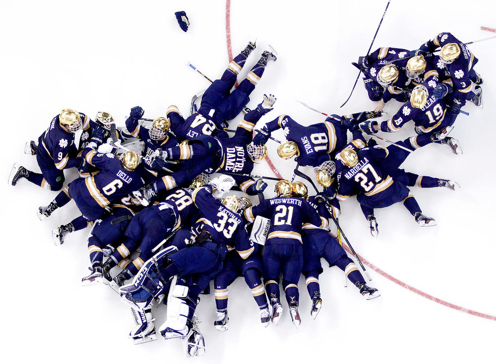 Notre Dame players pile up after  Andrew Oglevie  (15) scored the game-winner in overtime to send Notre Dame to the Frozen Four at SNHU Arena in Manchester, NH on March 26, 2017.    This image won PDN's (Photo District News) Adrenaline 2018 competition, linked  here .