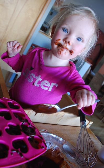 Quite the helper. sadie spoons on chocolate sauce after licking the whisk.