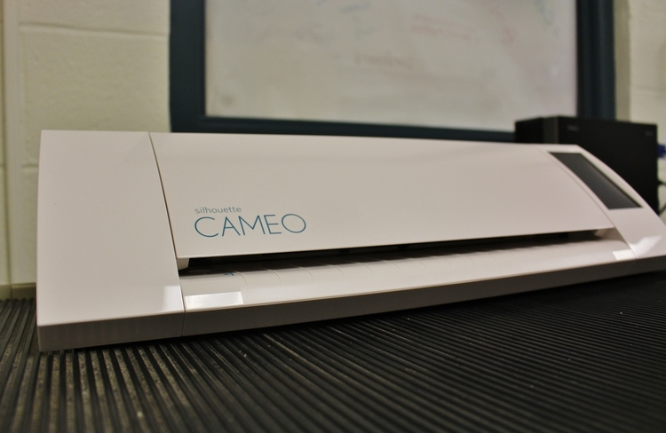 The Silhouette Cameo (pictured above) is a paper cutter that can cut intricate designs as pictured in the image at the top of this page.