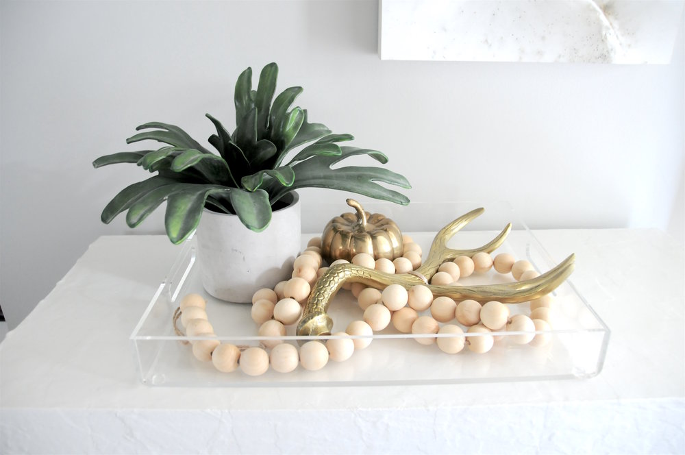 Acrylic Tray- West Elm, wood beaded garland- Shop Nest TO, Faux succulent $14.99 + Brass Antler $9.99 + Pumpkin $4.99- Marshalls