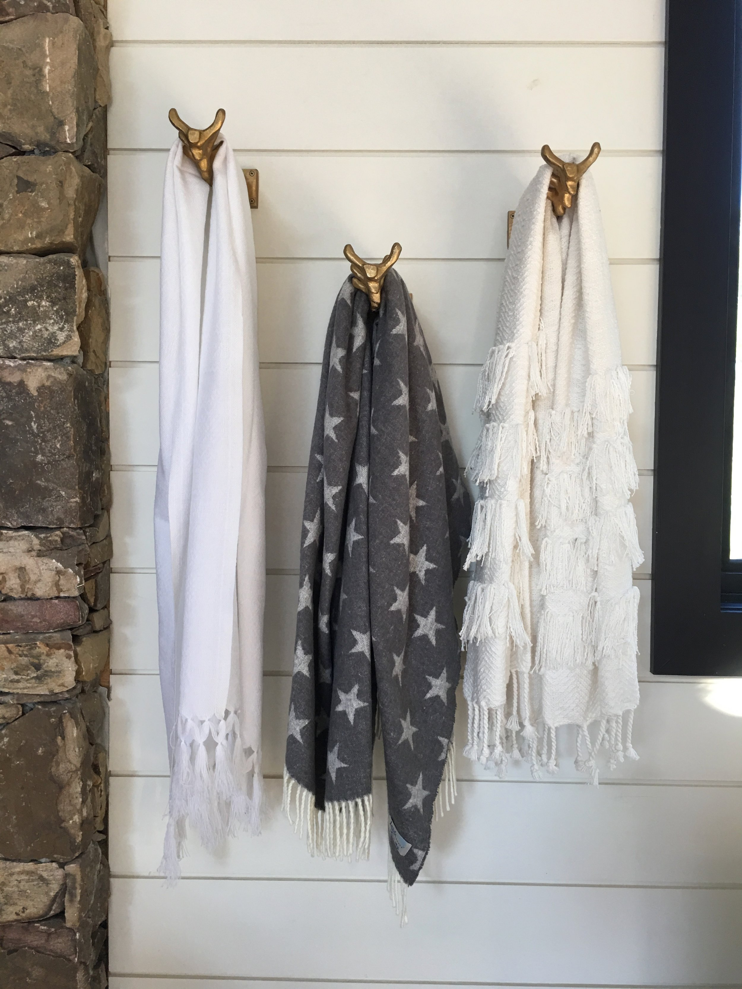 White and Grey towels on gold wall hooks