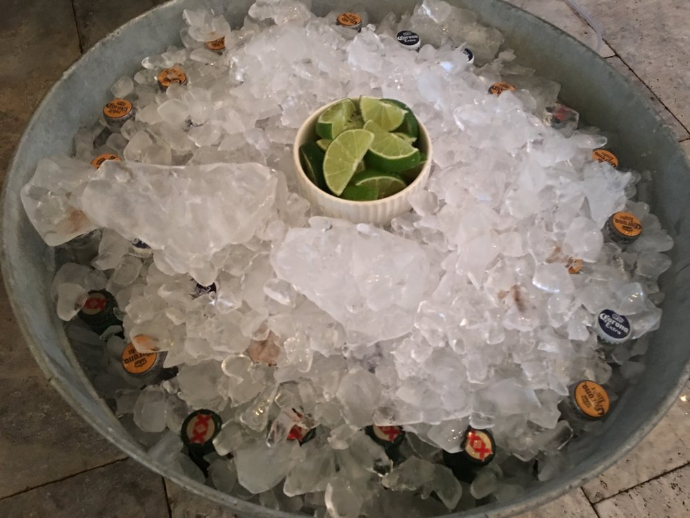 Galvanized bucket with beers on ice and lime wedges