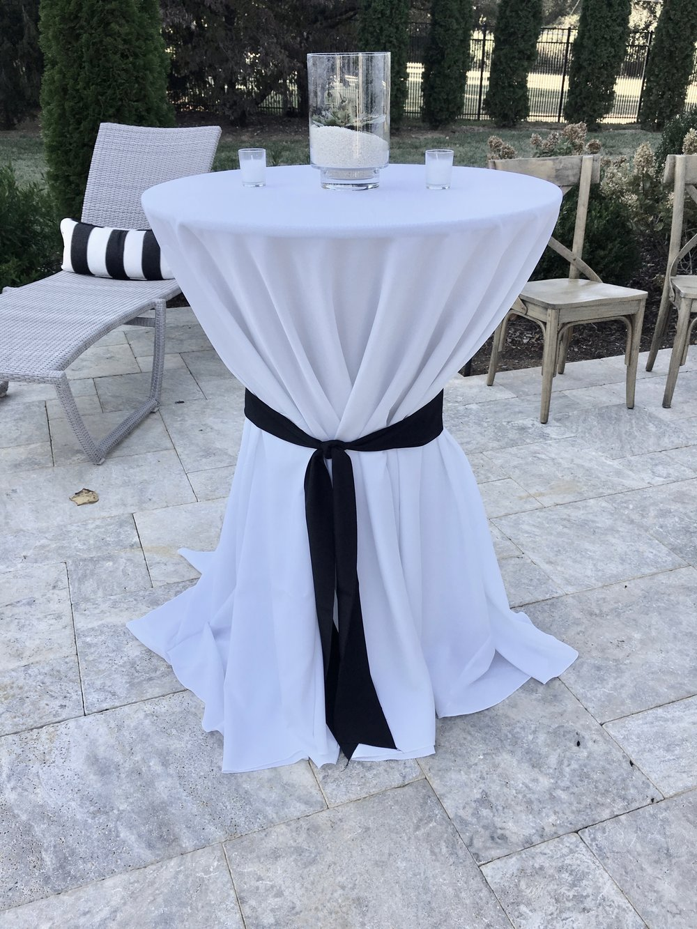 Bar Height Table with White Tablecloth black ribbon and succulent centerpiece
