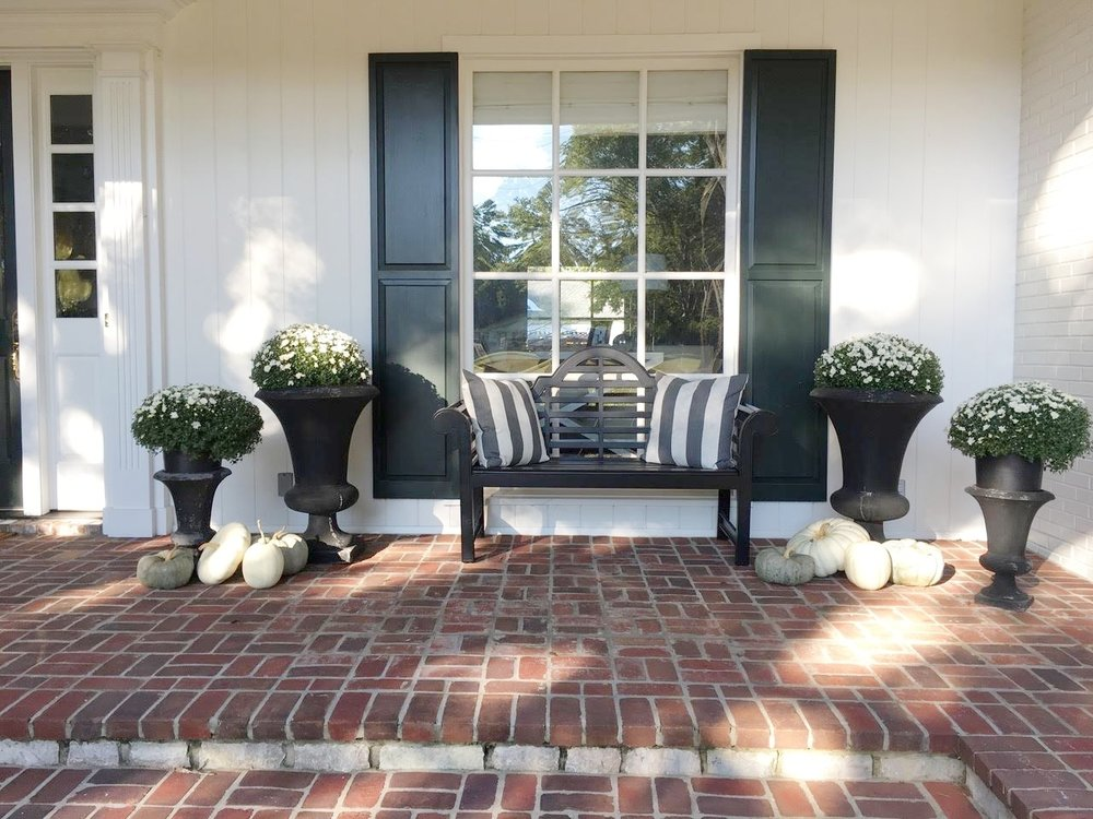 Fall Front Porch Decorations black bench with white mums and gray, white and green pumpkins