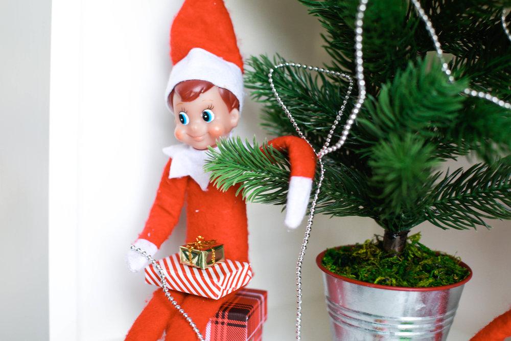 Close up of boy elf at christmas tree.jpg
