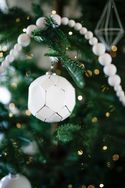 White geometric ornament on aspen balsam fir, simple modern christmas decor