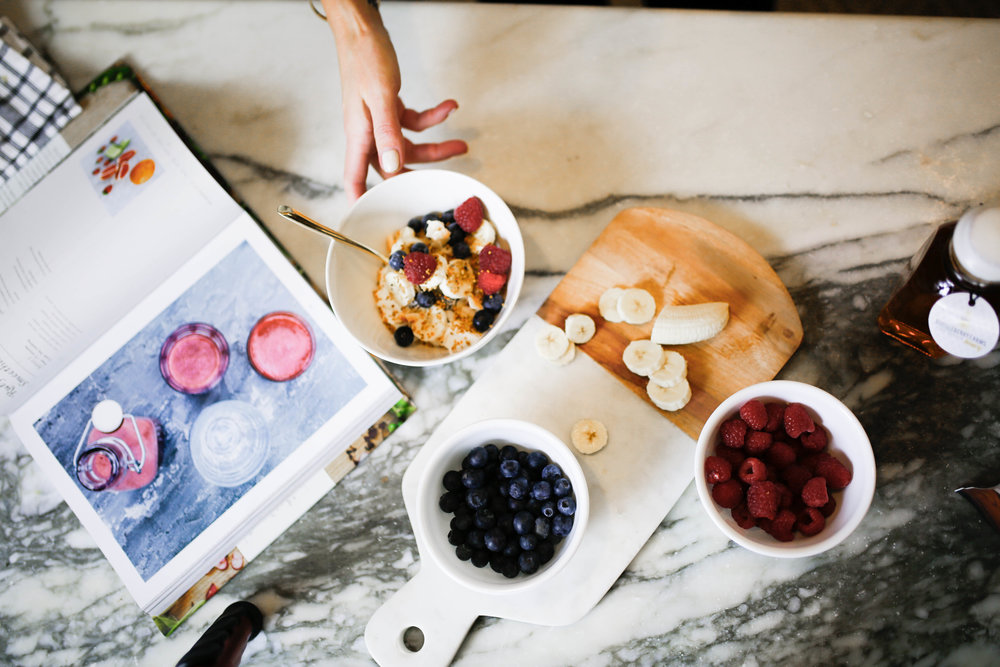 making a healthy breakfast with berries on a marble cutting board