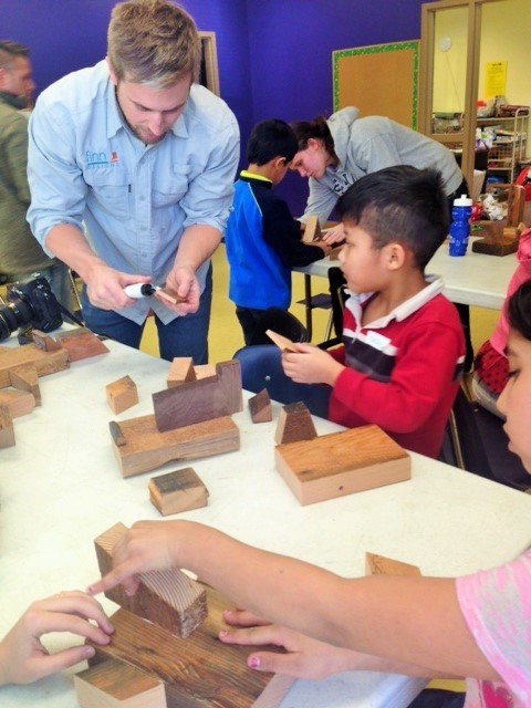 Finnu Wood Design's Josh Humble assisting Little Learners program students with a creative reclaimed wood sculpture project. (Photo courtesy of CHARISM)