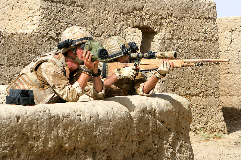 British marine Sgt. Gareth Beardshaw looks through his binoculars and gives distance readings to Color Sgt. Jason Walker as the sniper team returns enemy fire in Lakari Bazaar, Afghanistan, July 19, 2009. Image courtesy of United States Marine Corps , Creative Commons.