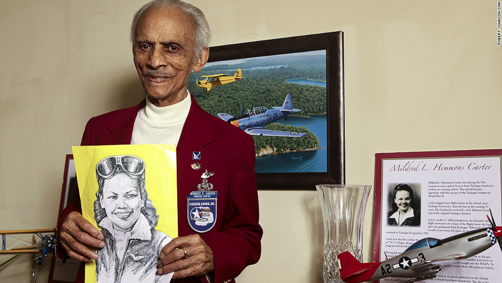 "Herbert Carter, 94, one of the original 33 Tuskegee Airmen pilots, holds a portrait of his wife, Mildred Hemmon Carter, in her flight uniform. She was the first black female pilot in Alabama and is counted among the history-making Tuskegee Airmen, too. He eventually rose to the rank of lieutenant colonel. Married nearly 70 years, the two were known as Tuskegee's ""first couple""."