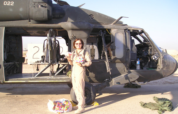 Tammy Duckworth stands outside a Black Hawk helicopter like the one she was in when she was shot down Nov. 12, 2004. She's holding bags of candy and school supplies intended for Iraqi children. (Photo credit: DailyHerald.com)