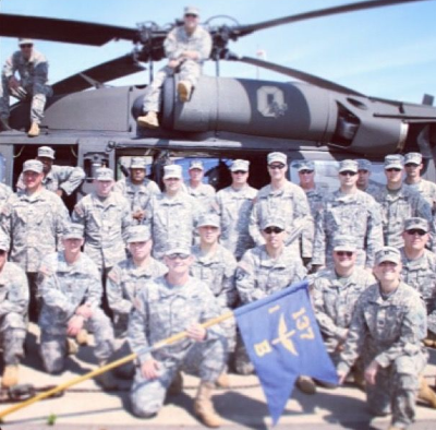 Captain Gahn, bottom right, holding the edge of the flag, served as Commander of Bravo Company, 1-137th Aviation Regiment. (Photo credit: Miranda Gahn)