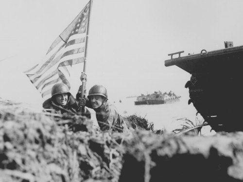 U.S. Marines Captain Paul S. O'Neal (USMC) and Captain Milton F. Thompson plant the American flag on Guam just after the Marines and Army assault troops landed. (Photo credit: U.S. Army Archives)