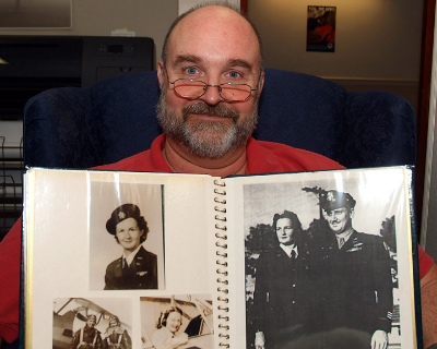 Rich Williams holds a scrapbook full of photos of his mother as a WASP (Photo credit: Air Force/Keith Keel)