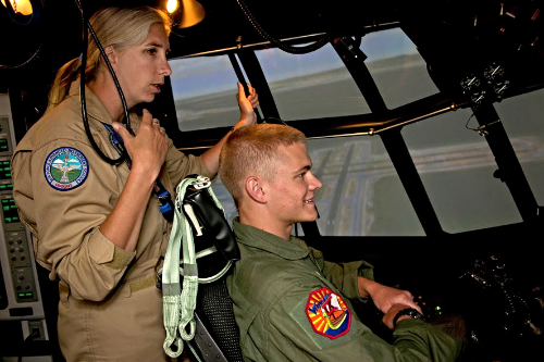 USAF Cadet Joseph Euhus takes the controls of a C-130 simulator as Regina Mizell, 23rd Operation Support Squadron C-130 flight simulator instructor, watches on. USAF photo/Airman 1st Class Benjamin Wiseman)