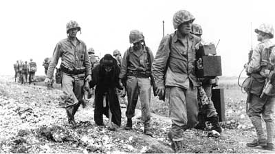Marines help an aged Okinawan to safety as a third Marine of the party carries the man's meager possessions. (Photo: Dept of Defense/USMC)