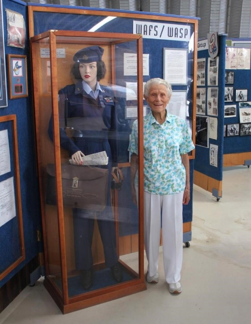 Iris standing next to a display of her old uniform at the P-38 Museum in Riverside. (Photo: The Press-Enterprise)