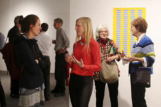 Emily Manning-Mingle (CFA'09,'10) (left) with Cole (center, in red) at the opening reception for Hannah Cole: Caring for Surfaces, on November 6. Photo by Smaranda Tolosano (CAS'16)